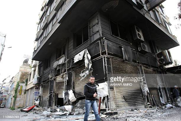 A man walks past a burntout building in the Northern city of Latakia some 350 km northwest Damascus on March 27 2011 Syrian security forces strove to...
