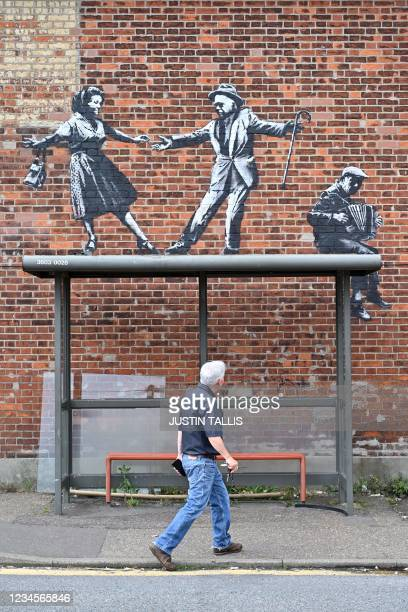 Man walks past a bus stop below a graffiti artwork of a couple dancing to an accordion player, which bears the hallmarks of street artist Banksy, on...