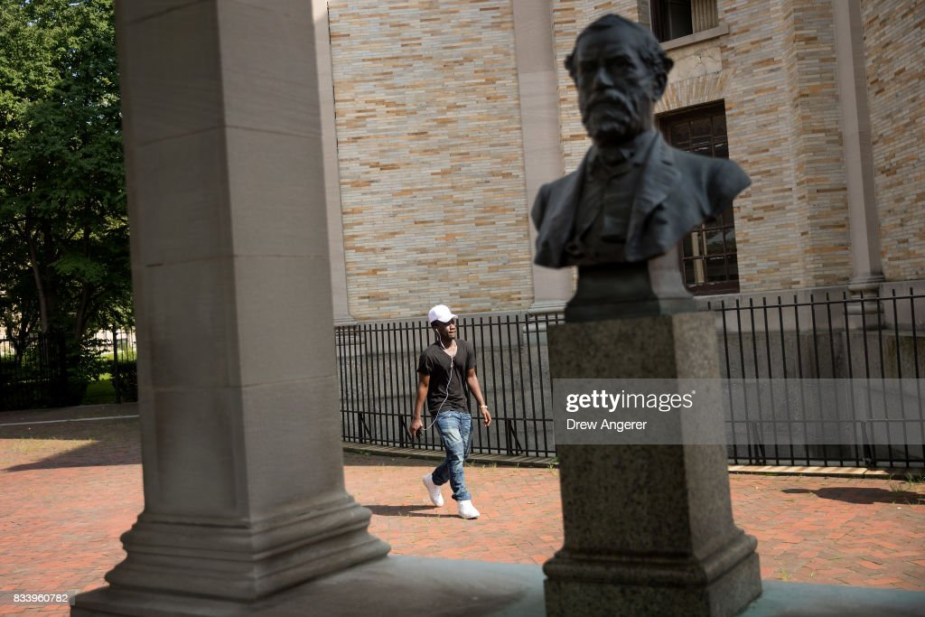 A man walks past a bust of Robert E. Lee as it stands in the 'Hall of Fame for Great Americans' on the campus of Bronx Community College, August 17, 2017 in the Bronx borough of New York City. On Wednesday night, the school announced the statues of Robert E. Lee and Confederate general Stonewall Jackson will be replaced and removed.