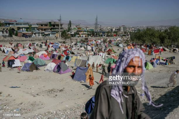 Man walks past a camp of internally displaced people in Kabul on September 17, 2021.