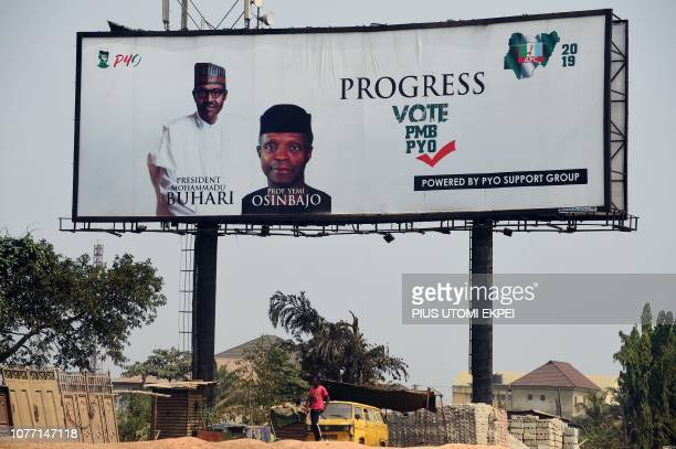 TOPSHOT A man walks past a campaign billboard for Nigeria's incumbent president and candidate to his reelection for the ruling All Progressives...