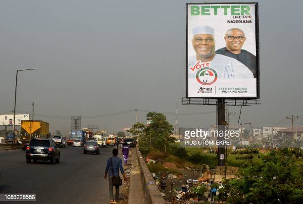 A man walks past a campaign billboard of presidential candidate from the opposition People's Democratic Party Atiku Abubakar and his running mate...