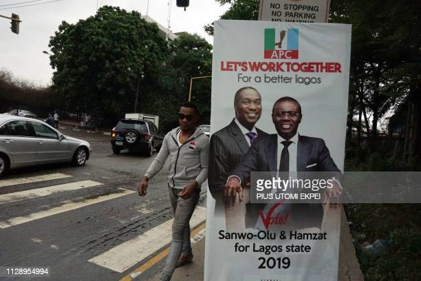 A man walks past a campaign poster of gubernatorial candidate of the ruling All Progressives Congress party in Lagos Babajide SanwoOlu and his...
