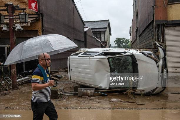 Man walks past a car that was overturned after the nearby Kuma River burst its banks, on July 5, 2020 in Hitoyoshi, Japan. Around 16 people are...