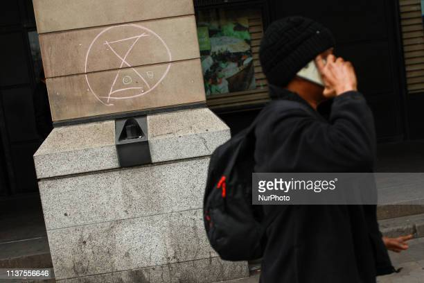 A man walks past a chalk symbol for climate change activist group Extinction Rebellion outside Westminster tube station in London England on April 16...