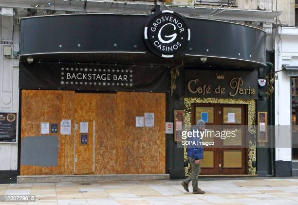 Man walks past a closed and boarded up Cafe de Paris. England remains under lockdown as the Prime Minster Boris Johnson refuses to rule out that it...