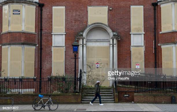Man walks past a closed and boarded up police station in Hackney as extra police officers have been deployed after a recent rise in killings in the...