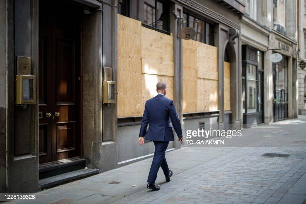 A man walks past a closed and boarded up restaurant in the City of London on August 21 2020 British government debt has exceeded £20 trillion for the...