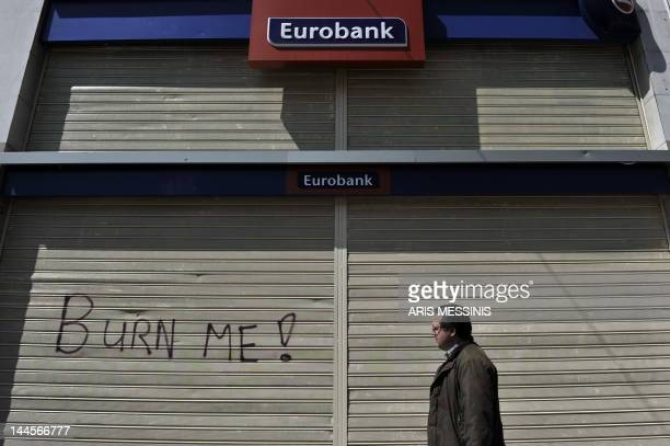 A man walks past a closed bank during a 24 hour strike in Athens on May 11 2011 The government has now rolled out a new programme to economise some...