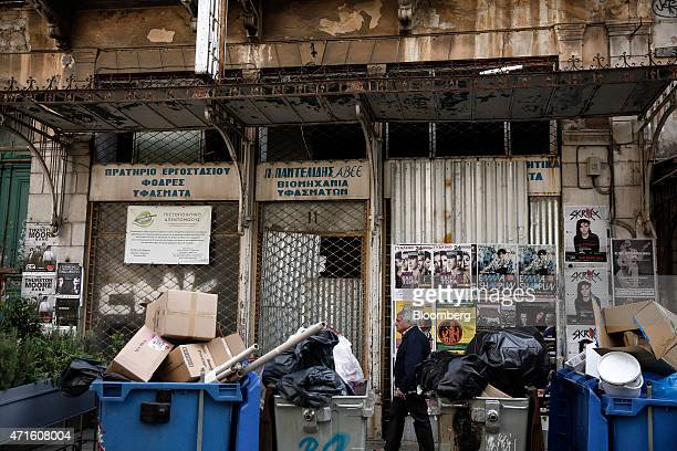 A man walks past a closed fabric manufacturer in the Agia Irini district of Athens Greece on Saturday April 25 2015 The downturn that decimated the...