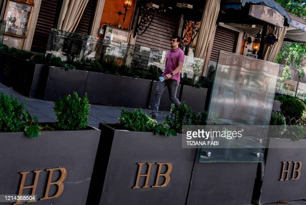 Man walks past a closed Harry's Bar on Via Veneto in central Rome on May 21 as the country eases its lockdown aimed at curbing the spread of the...