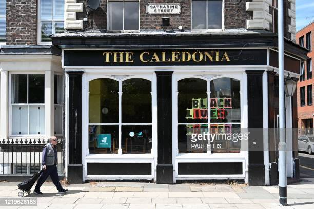 Man walks past a closed pub where a Black Lives Matter poster has been displayed in a window in Liverpool, north-west England on June 13, 2020.