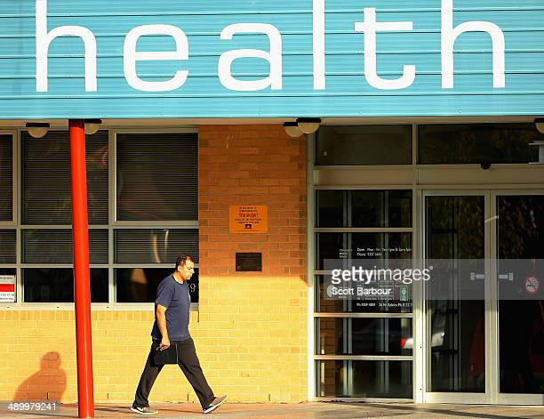 A man walks past a Community Health Centre on May 13 2014 in Melbourne Australia Tony Abbott's Coalition government will deliver it's first federal...