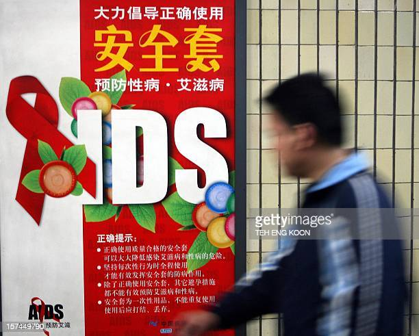 A man walks past a condom advertisment billboard on display in Beijing 12 April 2007 About 350 people infected with HIV/AIDS were blocked by police...