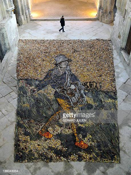 A man walks past a creation representing 'The sower' of Vincent Van Gogh made by Brazilian artist Vik Muniz with branches leaves and dried flowers...