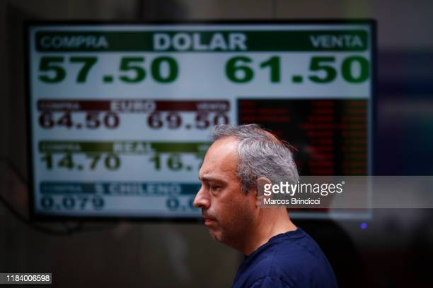 Man walks past a currency exchange house showing updated prices of Dollars Brazilian reais Chilean pesos and Euros on October 28 2019 in Buenos Aires...