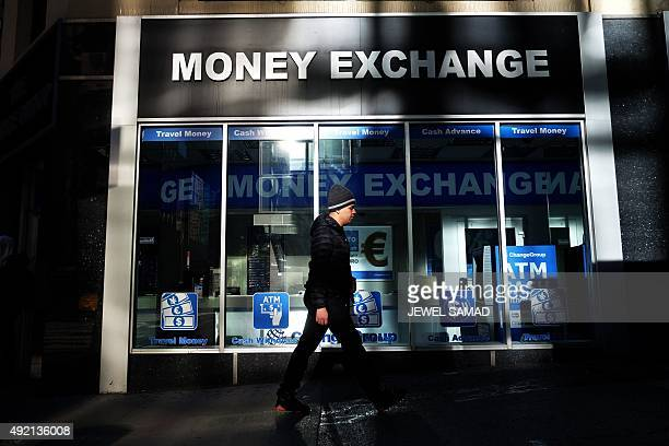 A man walks past a currency exchange office in New York on October 10 2015 AFP PHOTO/JEWEL SAMAD