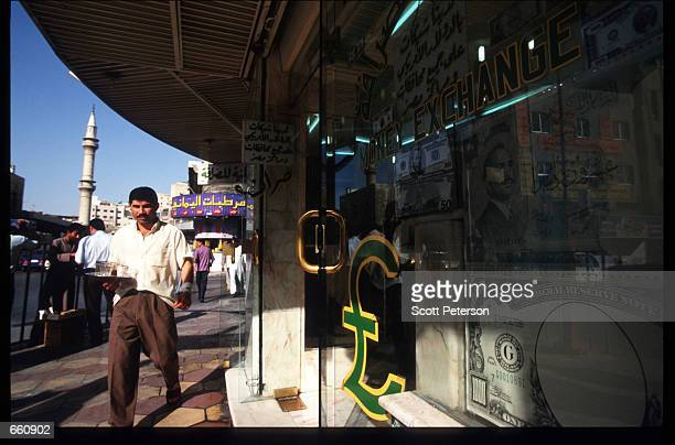 A man walks past a currency exchange office May 17 1998 in Amman Jordan Still a teenager when crowned in 1952 King Hussein has led the young Arab...