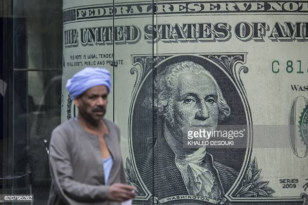 A man walks past a currency exchange shop displaying a giant US dollars banknote in downtown Cairo on November 3 2016 Egypt floated the country's...