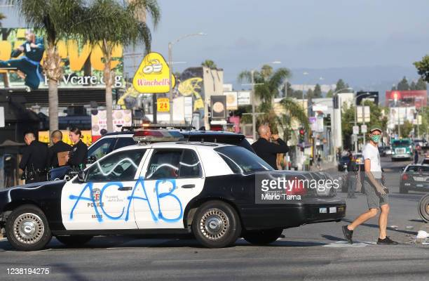 Man walks past a defaced LAPD vehicle in the Fairfax District, an area damaged during yesterday's unrest, following violent demonstrations in...