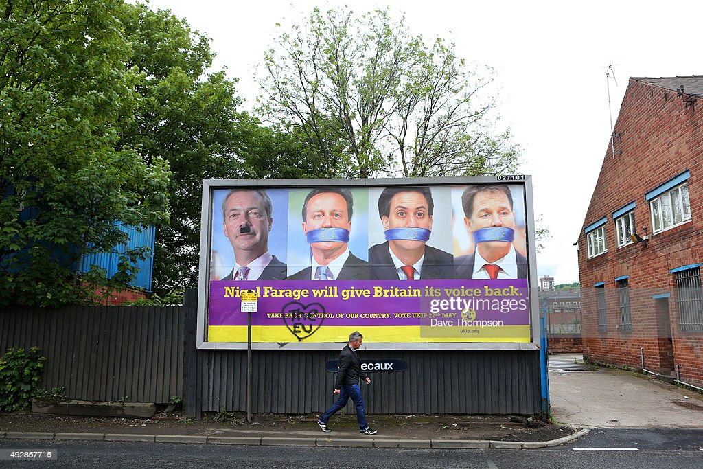 A man walks past a defaced UKIP poster on May 22, 2014 in Sheffield, England. Voters across Europe are taking to the polls to vote in the elections for the European Parliament as well as local council elections in England and Northern Ireland.