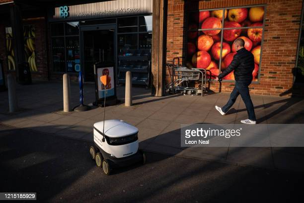Man walks past a delivery robot as it makes a home delivery on March 27, 2020 in Milton Keynes, England. With the country currently under a lockdown...