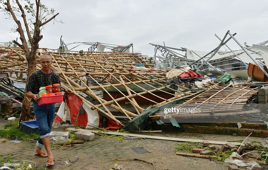 A man walks past a destroyed building in Xiamen in China's eastern Fujian province after Typhoon Meranti made landfall on September 15, 2016. Typhoon Meranti made landfall in Fujian early September 15, 2016, with winds up to 230kph, knocking out electricity in some areas and causing rail delays. / AFP / STR / China OUT