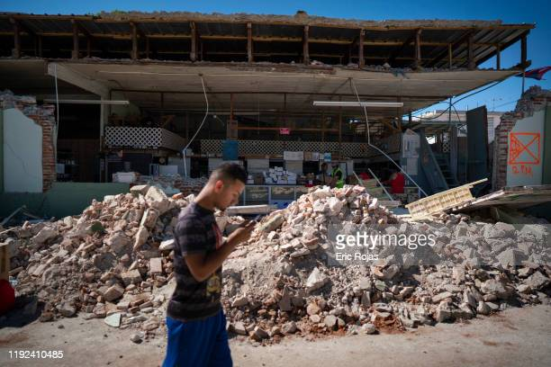 A man walks past a destroyed store after a 64 earthquake hit just south of the island on January 7 2020 in Guánica Puerto Rico This morning's...