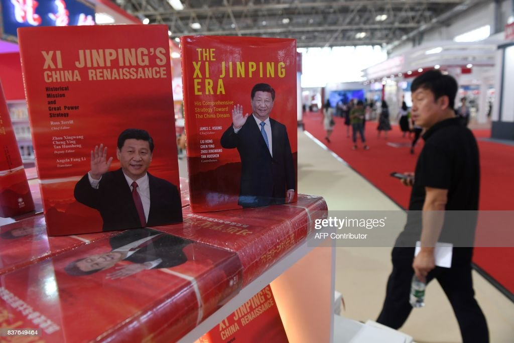 A man walks past a display of books about China's President Xi Jinping at the Beijing International Book Fair in Beijing on August 23, 2017. The book fair runs from August 23 to 27. / AFP PHOTO / Greg Baker