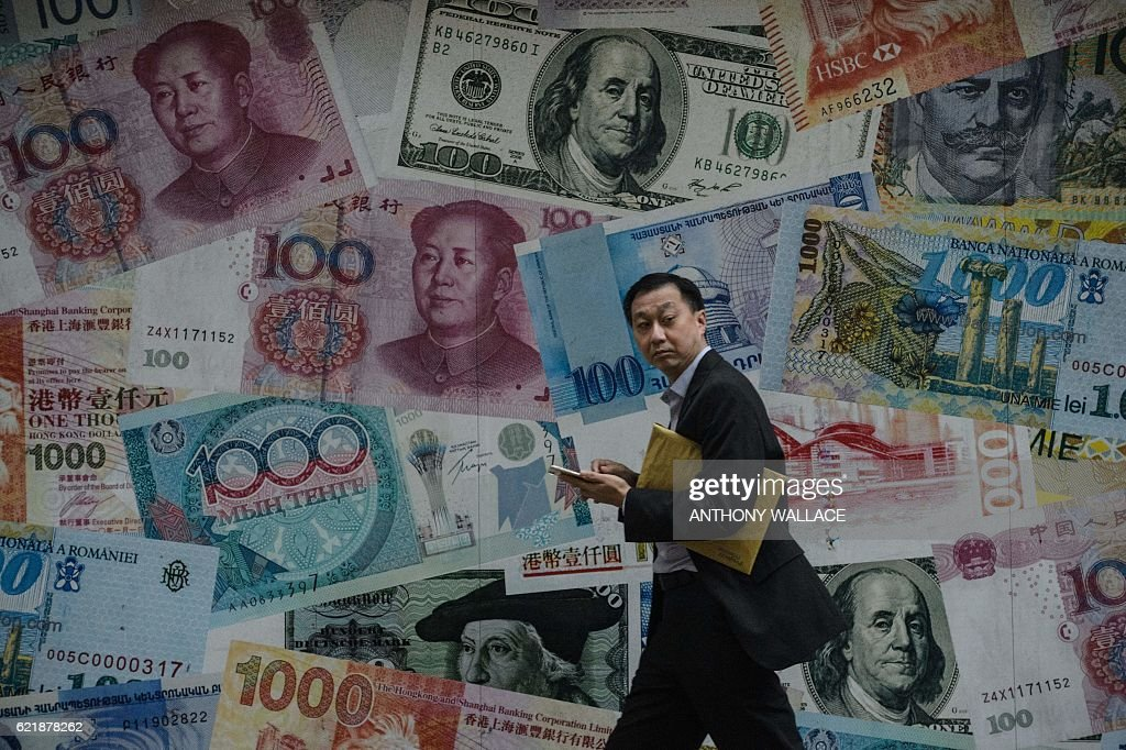 A man walks past a display showing bank notes of different currencies in Hong Kong on November 9, 2016. Share markets plunged on November 9 and the dollar tumbled against the yen and the euro as Donald Trump was elected US president, in a stunning upset with major implications for the world economy. / AFP / Anthony WALLACE