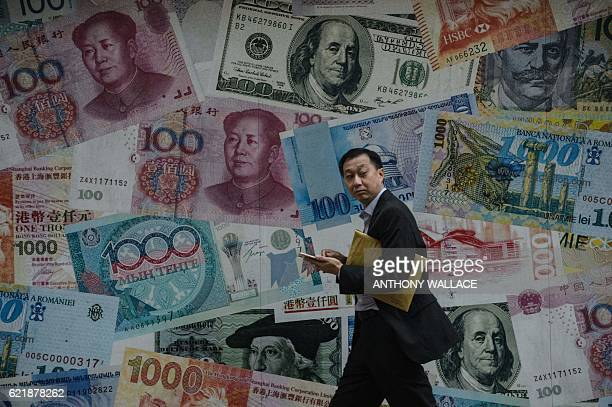 A man walks past a display showing bank notes of different currencies in Hong Kong on November 9 2016 Share markets plunged on November 9 and the...