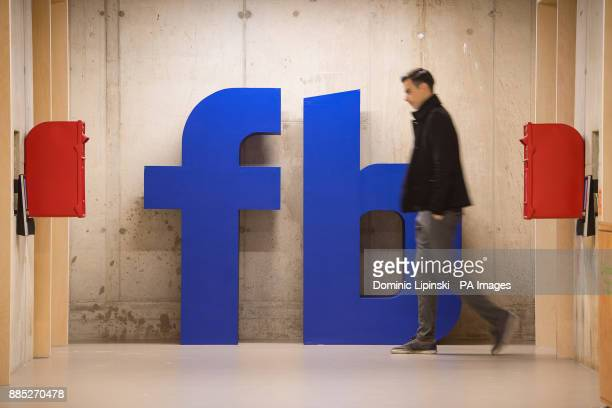 Man walks past a Facebook logo at Facebook's new Frank Gehry-designed headquarters at Rathbone Place in London.