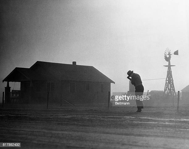 A man walks past a farmhouse in a dust storm at the height of the Dust Bowl
