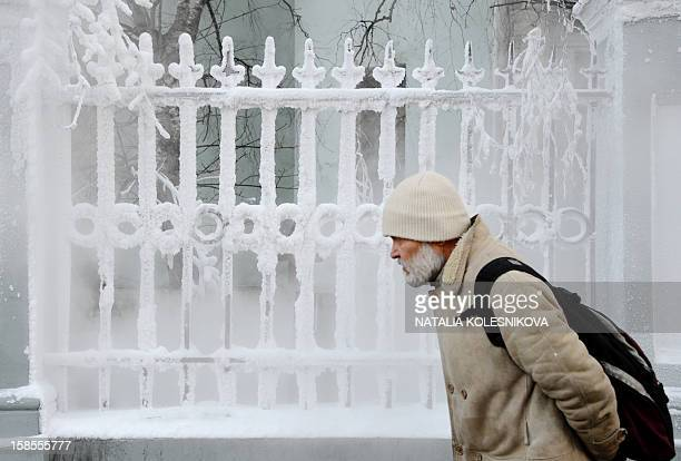 KOLESNIKOVA A man walks past a fence covered with hoarfrost in central Moscow on December 19 2012 A cold wave of weather hit this week the Russian...