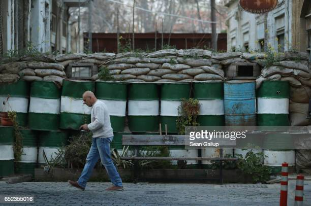 A man walks past a fortified position along the buffer zone on the southern Greek side of the divided city on March 6 2017 in Nicosia Cyprus Nicosia...