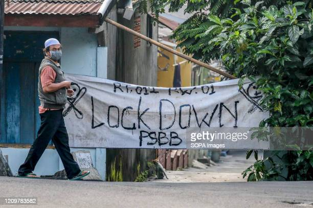 A man walks past a gate of a housing complex closed with a banner that says Lock Down as an effort to prevent the spread of COVID19 in Jakarta...