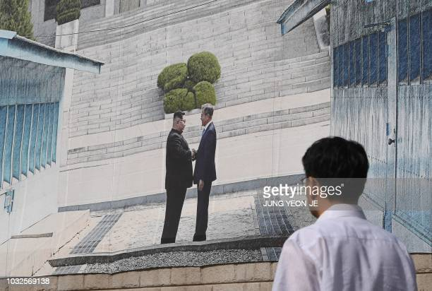 Man walks past a giant banner showing a picture of the summit handshake between South Korean President Moon Jae-in and North Korean leader Kim Jong...