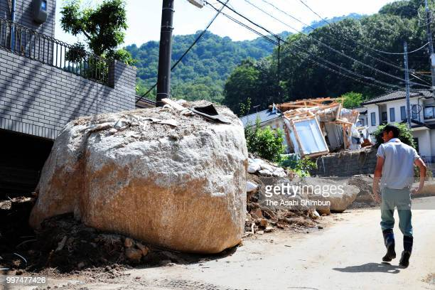 A man walks past a giant rock flown by a landslide on July 13 2018 in Hiroshima Japan The death toll from the torrential rain in western Japan due to...