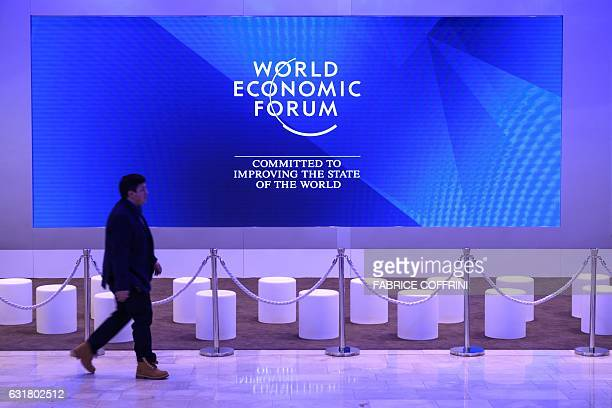 A man walks past a giant screen of the Davos Congress Center on the eve of the opening day of the World Economic Forum on January 16 2017 in Davos...