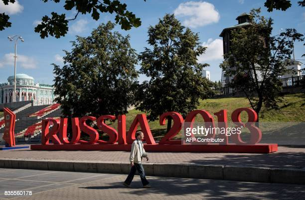 A man walks past a giant sign reading 'Russia 2018' in downtown Yekaterinburg on August 19 2017 The city of Yekaterinburg will host several games of...