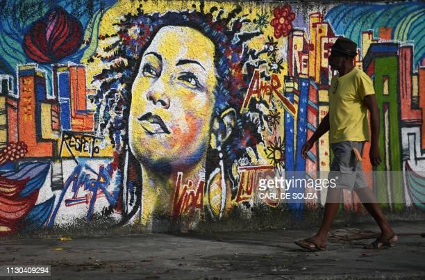 A man walks past a graffiti depicting Brazilian slain Brazilian councilwoman Marielle Franco near the site where she was murdered in Rio de Janeiro...