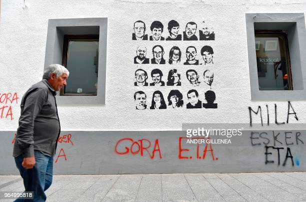 A man walks past a graffiti depicting portraits of Basque separatist group ETA prisoners and reading Long life ETA thanks a lot in the Spanish Basque...