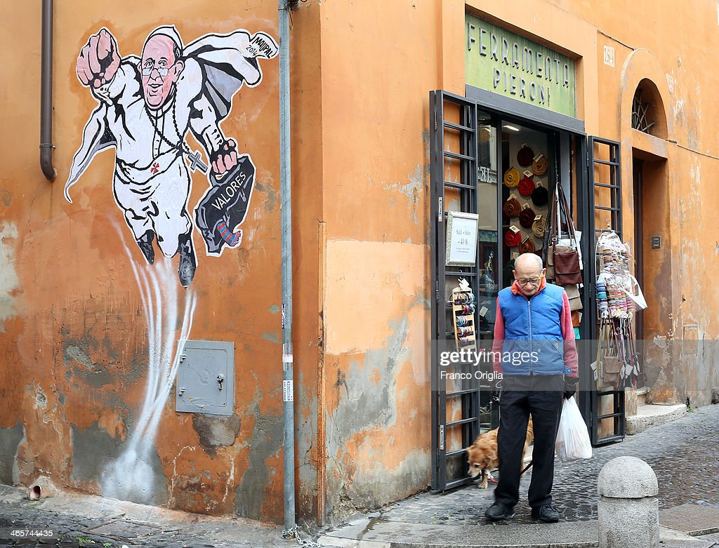 A man walks past a graffiti featuring a 'superhero' version of Pope Francis appears in Borgo Pio, next to St. Peter's Square on January 29, 2014 in Rome, Italy. The image started circulating from the twitter account of the Vatican and has rapidly spread around the world.