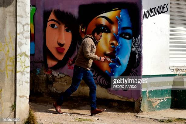 A man walks past a graffiti in Tenancingo Tlaxcala state Mexico on January 19 2018 The most powerful pimps of Mexico have virtually built walls...