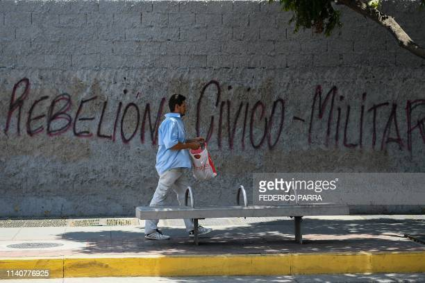 TOPSHOT A man walks past a graffiti reading Civic and military rebellion in Caracas on May 2 2019 Two more opposition demonstrators both minors have...
