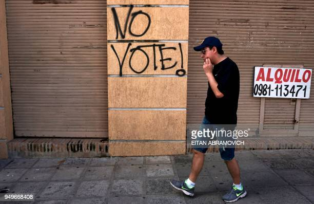 A man walks past a graffiti reading 'Do not vote' ahead of the upcoming April 22 presidential elections in Asuncion on April 21 2018 Opinion polls...