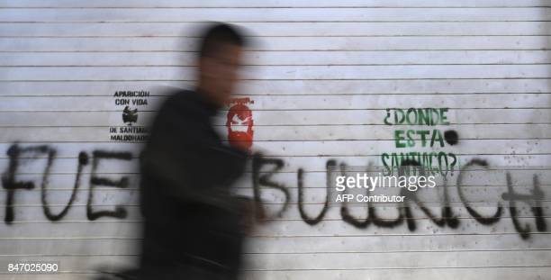 A man walks past a graffiti reading 'Where is Santiago ' disappeared on August 1st during a Mapuche protest in Chubut province near Plaza de Mayo...