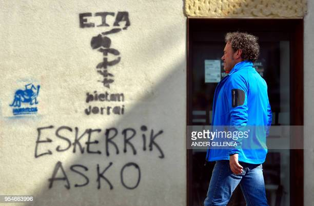 A man walks past a graffiti showing the Basque separatist group ETA logo and the text in Basque Thanks a lot in the Spanish Basque village of...