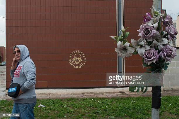 IDE A man walks past a graffity reading 'Attention polluted city' in the Tamburi district of Taranto on March 18 2015 The site in Taranto in the...