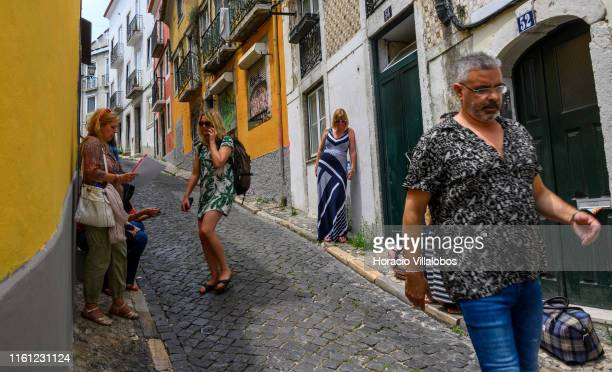 A man walks past a group of tourists waiting to be let in into their rented apartment in Calçada Salvador Correia de Sa Santa Catarina historical...